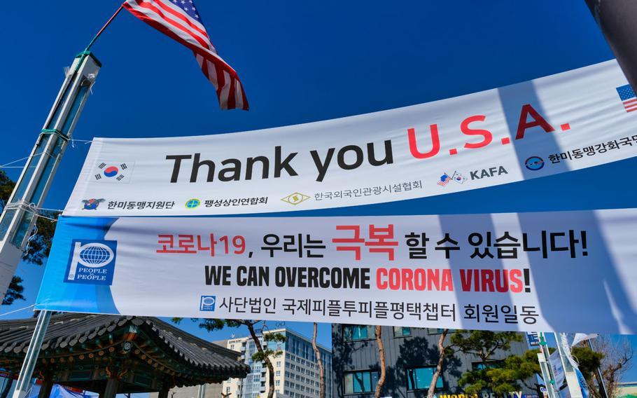 An American flag waves alongside coronavirus banners outside Camp Humphreys, South Korea, March 16, 2020.