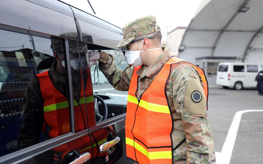 A soldier takes the temperature of a driver at Camp Zama, Japan, March 31, 2020 to screen for coronavirus.