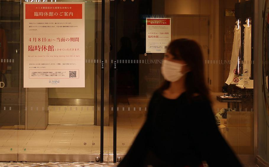 A woman strolls past a Tokyo department store that's closed because of the coronavirus, April 9, 2020.