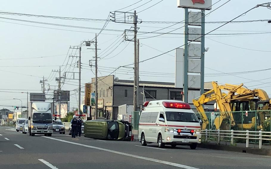 Japanese first responders tend to a local man whose vehicle toppled over in Sagamihara, Japan, Friday, June 5, 2020.