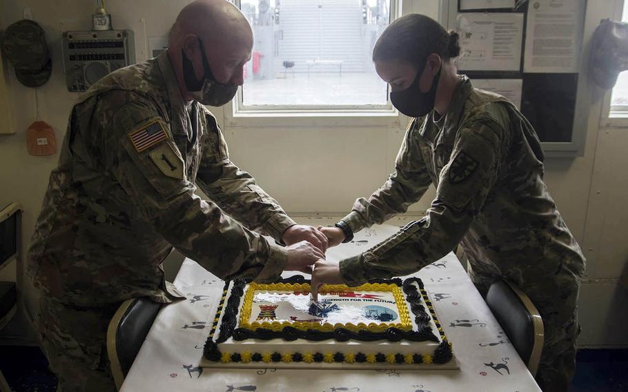 Sgt. 1st Class Vincent Passero, 49, and Pvt. Courtney Pearson, 19, cut a cake in celebration of the Army's 245th birthday aboard the Army Vessel Harpers Ferry at Yokohama North Dock, Japan, Sunday, June 14, 2020.