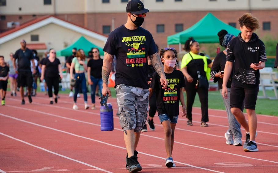 People walk the track at Balboni Field for 1,865 seconds, representing the year 1865, during the inaugural Juneteenth celebration at Camp Humphreys, South Korea, Friday, June 19, 2020.