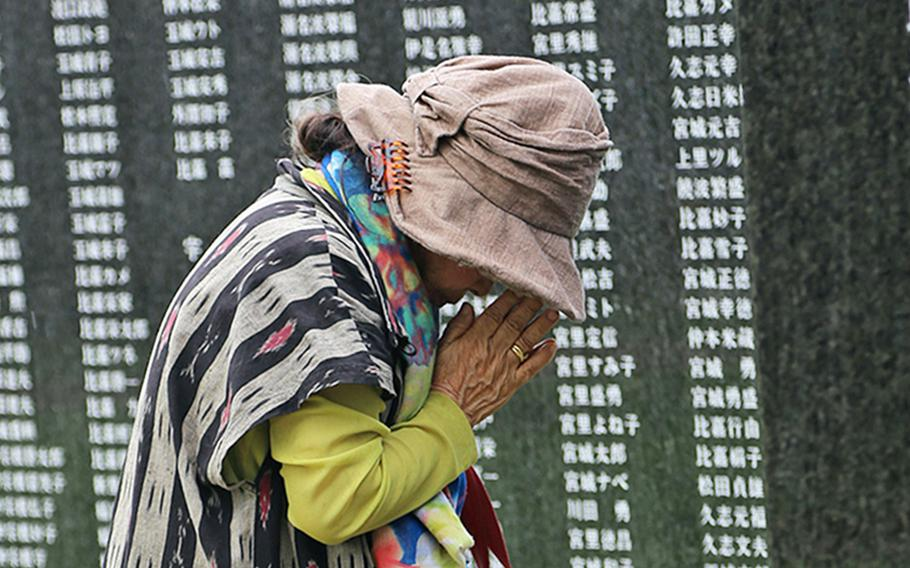 A woman prays for loved ones lost in the Battle of Okinawa during the annual Irei no Hi ceremony at Peace Memorial Park in Okinawa, Japan, June 23, 2019. This year's ceremony was scaled down because of coronavirus concerns.