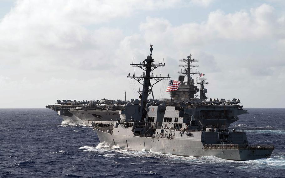 The guided-missile destroyer USS Ralph Johnson steams in formation with the aircraft carrier USS Nimitz in the Philippine Sea, June 23, 2020.
