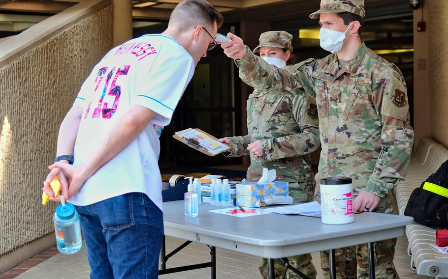 An airman is screened for coronavirus symptoms by 51st Fighter Wing medical staff before he enters Osan Air Base, South Korea, April 3, 2020.
