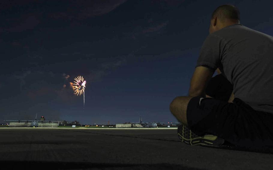 Fireworks explode behind C-130J Super Hercules aircraft at Yokota Air Base, Japan, Thursday, July 2, 2020.