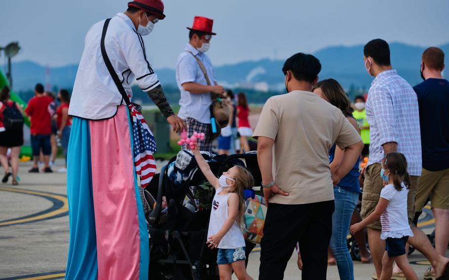 A balloon artist gives a balloon shaped like a dog to a young girl at Liberty Fest 2020 on Osan Air Base, South Korea, Saturday, July 4, 2020.