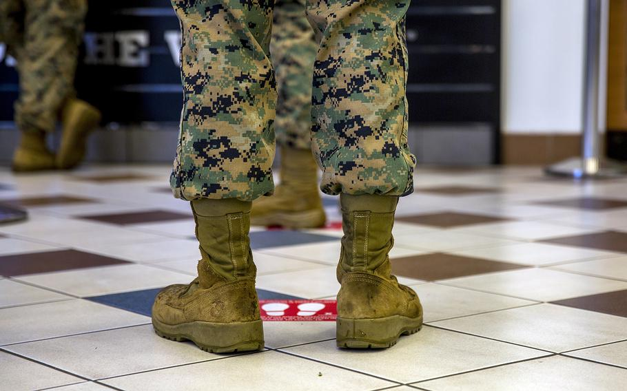 A Marine stands behind a social distancing floor marker while waiting in line at the exchange at Camp Hansen, Okinawa, April 7, 2020.