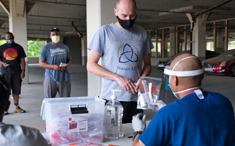 A service member receives a coronavirus test kit within hours of arriving at Osan Air Base, South Korea, Tuesday, July 14, 2020.