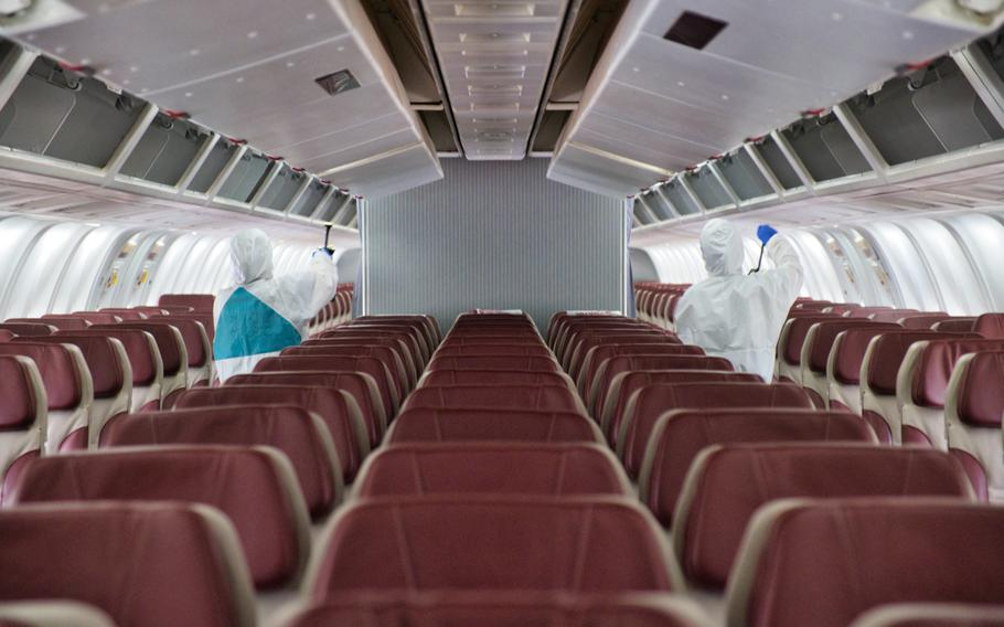 A sanitation crew works to disinfect the chartered Boeing 767 known as the Patriot Express at Osan Air Base, South Korea, Tuesday, July 14, 2020.