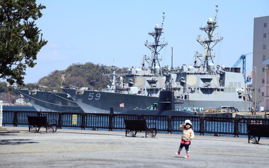 A child plays in a park across from the guided-missile destroyers USS. John S. McCain, left, and USS Russell at Yokosuka Naval Base, Japan, April 14, 2020.