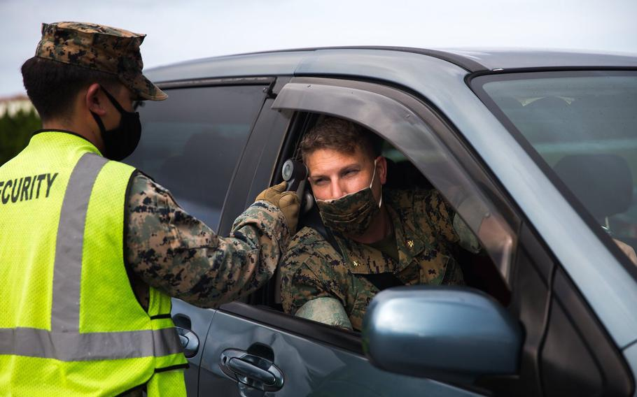 A Marine conducts a temperature check during a coronavirus screening at Camp Courtney, Okinawa, July 13, 2020.