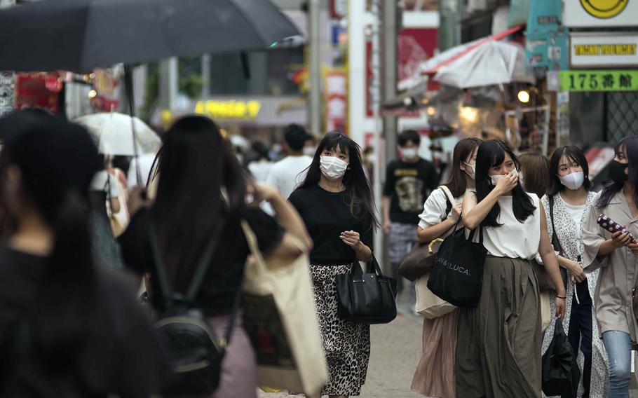 People wear masks as they stroll Takeshita Street, a pedestrian area lined with fashion boutiques, cafes and eateries in Harajuku, Tokyo, Monday, July 27, 2020.