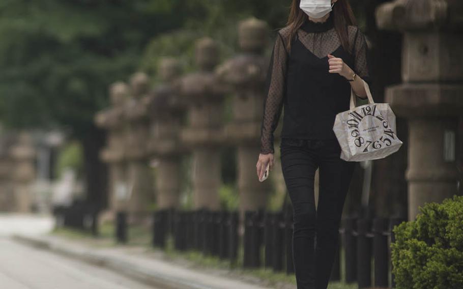A mask-wearing woman walks near Yasukuni Shrine in central Tokyo, Monday, July 27, 2020.