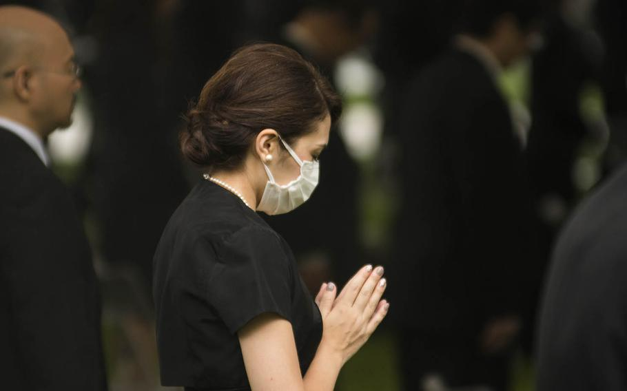 A woman prays at Hiroshima Peace Memorial Park, Thursday, Aug. 6, 2020, during a ceremony marking the 75th anniversary of the atomic bombing.