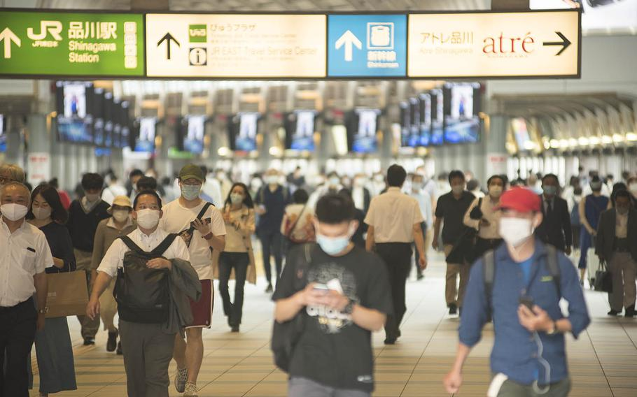 Commuters wearing masks make their way through Shinagawa Station on a recent afternoon in central Tokyo.
