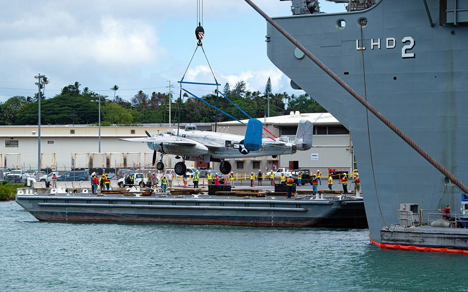 A World War II-era B-25 Mitchell bomber is lowered onto a dock at Joint Base Pearl Harbor-Hickam, Hawaii, Aug. 11, 2020.