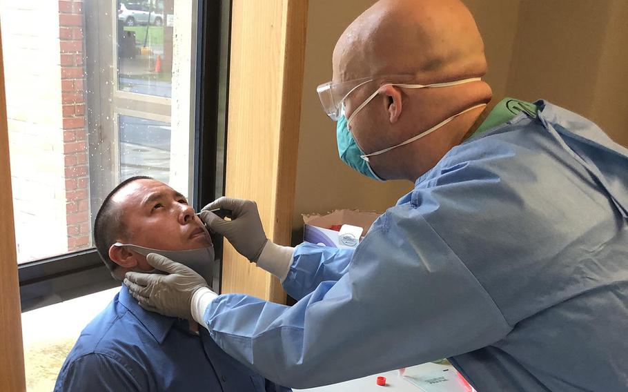 A medical professional from the 65th Medical Brigade conducts a nasal swab on an Eighth Army civilian employee who was selected randomly for Eighth Army COVID-19 Surveillance Testing Aug. 6 on Camp Humphreys, South Korea.
