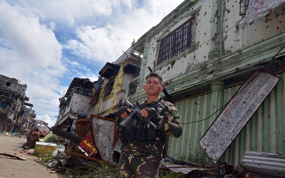 A Philippine soldier stands in Marawi, Philippines, following the city's liberation from Islamic extremists, Nov. 8, 2017.