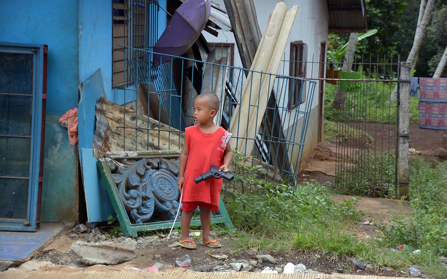 A child plays on a roadside near the city of Marawi, Philippines, in November 2017.