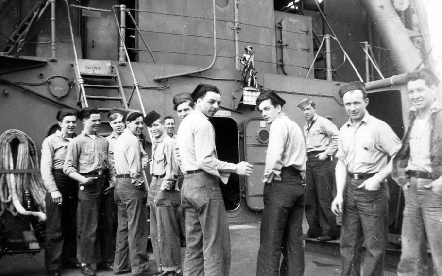 Crewmen of the USS Concord stand on the main deck below a statue of a minuteman mounted on the bulkhead, in this photo taken during the last 15 months of World War II.