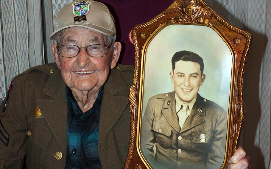 James Richardson, 99, a member of the famed Merrill's Marauders in Burma during World War II, poses with his daughter, Judy Robertson, in February 2020. He holds a photo of his brother, J.C., who was killed in France during the war.