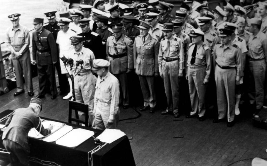 Gen. Douglas MacArthur and others watch as an Imperial Japan official signs a surrender document aboard the USS Missouri moored in Tokyo Bay, Sept. 2, 1945.