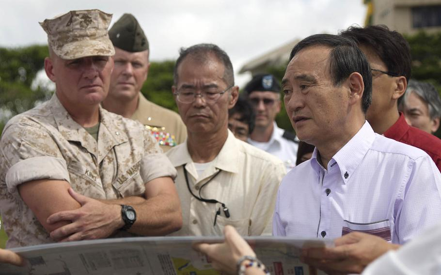 Then-Japanese Chief Cabinet Secretary Yoshihide Suga, right, visits Camp Kinser, Okinawa, Aug. 12, 2015. Suga became his country's 99th prime minister, Wednesday, Sept. 17, 2020.