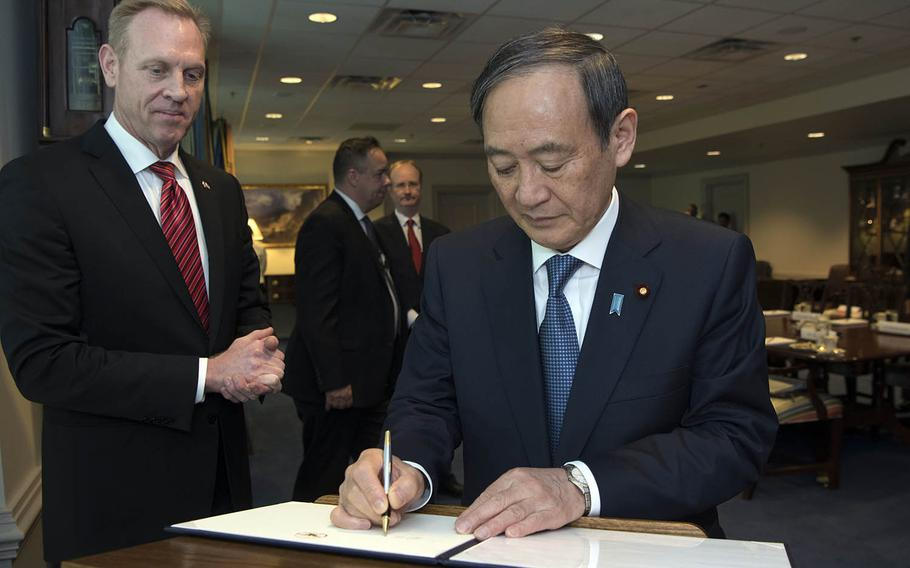 Then-Japanese Chief Cabinet Secretary Yoshihide Suga signs in a visitors book at the Pentagon in Washington, D.C., May 9, 2019. Suga became Japan's 99th prime minister on Wednesday, Sept. 16, 2020.