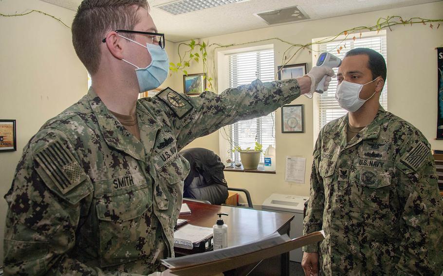 A sailor is screened for coronavirus symptoms at Sasebo Naval Base, Japan, May 13, 2020.