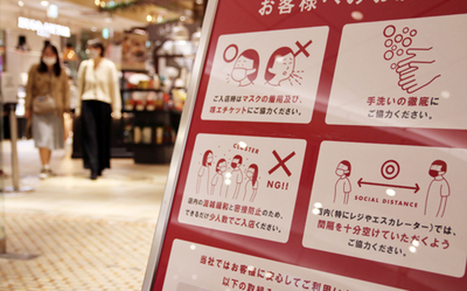A sign at a shopping area in central Tokyo reminds patrons to wear a mask, wash their hands and follow other anti-coronavirus measures, Tuesday, Nov. 17, 2020.