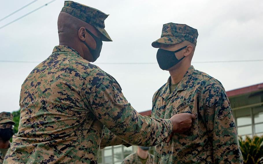 Staff Sgt. Billy Dixson, right, receives the Navy and Marine Corps Commendation Medal from Marine Corps Air Station Futenma commander Col. Henry Dolberry Jr., Nov. 13, 2020. Dixson was honored for saving a Japanese woman from drowning last month.