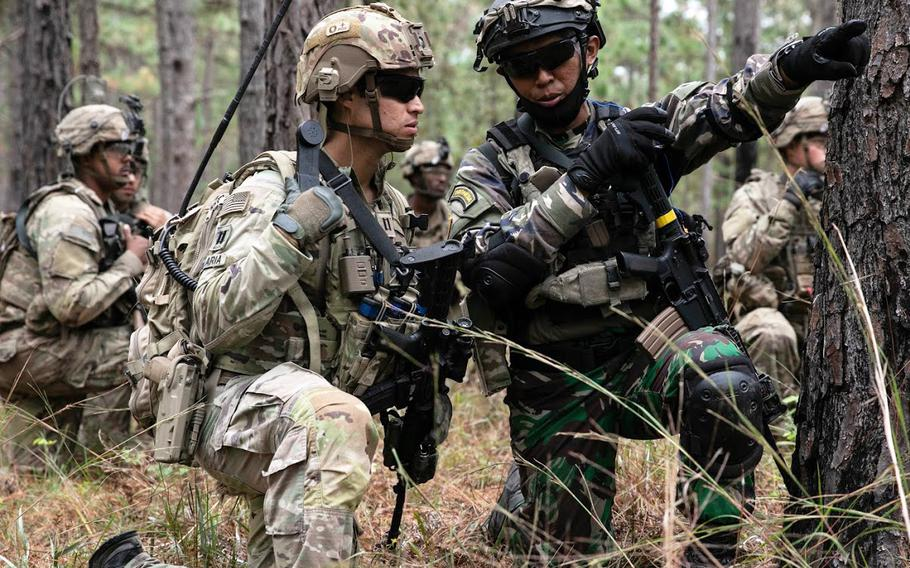 Capt. Kris Candelaria, a team leader from 2nd Battalion, 5th Security Force Assistance Brigade, and 1st Lt. Wilhelmus Raditya of Indonesia discuss plans for approaching an objective during a live-fire exercise at the Joint Readiness Training Center at Fort Polk, La., on Oct. 27, 2020.