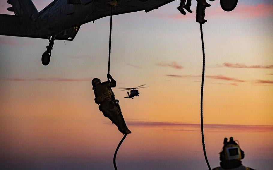 A member of the 15th Marine Expeditionary Unit fast-ropes from a Navy MH-60S Seahawk during training aboard the amphibious assault ship USS Makin Island in the Pacific Ocean, Oct. 29, 2020.