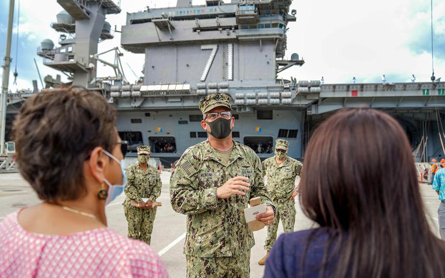 Guam Gov. Lou Leon Guerrero, left, listens as Rear Adm. John Menoni, commander of Joint Region Marianas, speaks outside the USS Theodore Roosevelt ahead of the virus-stricken carrier's departure from Naval Base Guam, June 4, 2020.