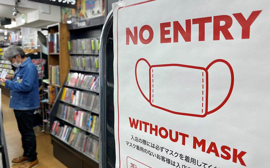 A sign outside a western Tokyo record store warns patrons not to enter without a mask, Sunday, Nov. 22, 2020.