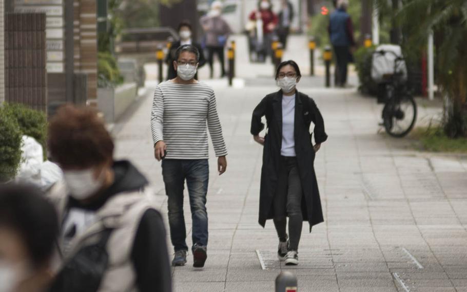 People wear masks to guard against the coronavirus while strolling in Yokohama, Japan, Nov. 20, 2020.