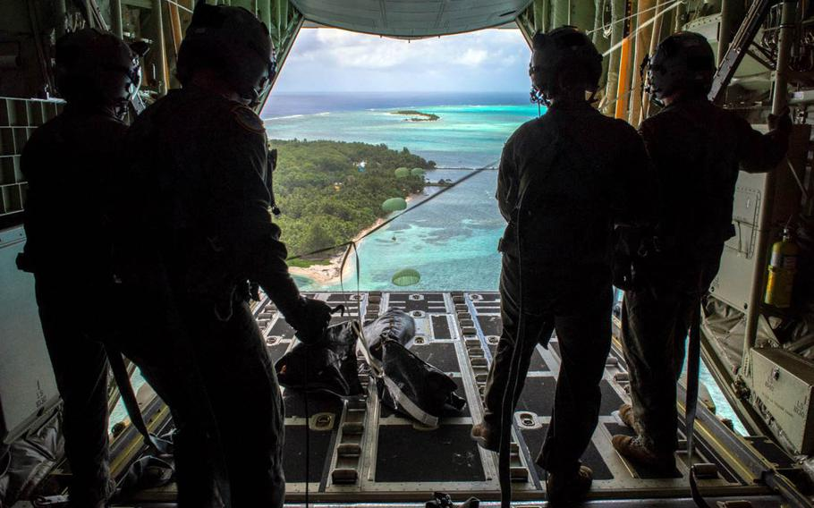 Loadmasters with the 36th Airlift Squadron out of Yokota Air Base, Japan, watch bundles parachute down to Nomwin, Federated States of Micronesia, Dec. 13, 2019, during the annual Operation Christmas Drop.
