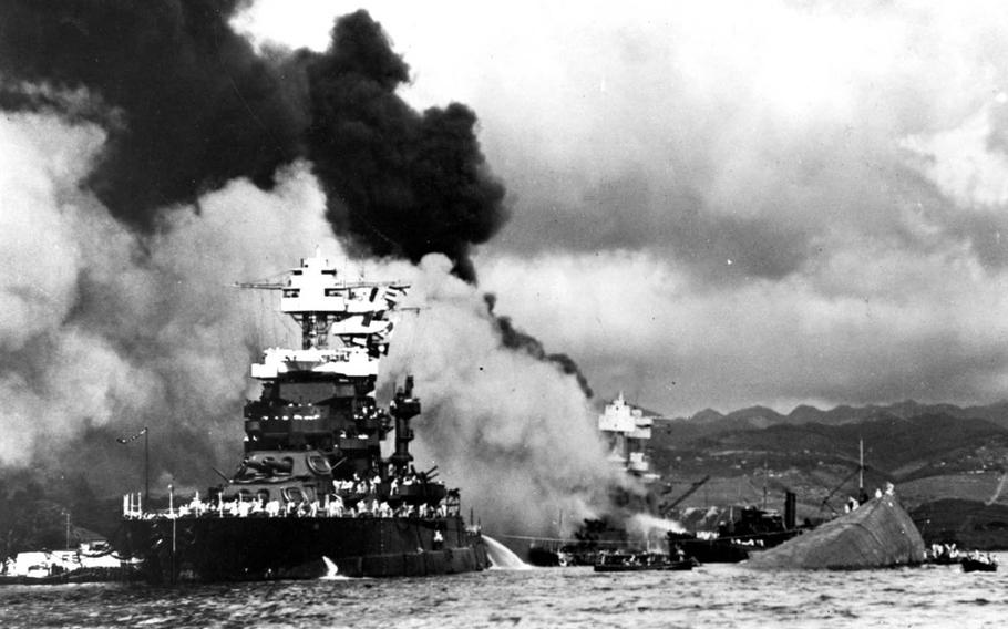 The USS Maryland floats beside the capsized USS Oklahoma, Dec. 7, 1941, as the USS West Virginia burns in the background following Japan's surprise attack on Pearl Harbor, Hawaii.