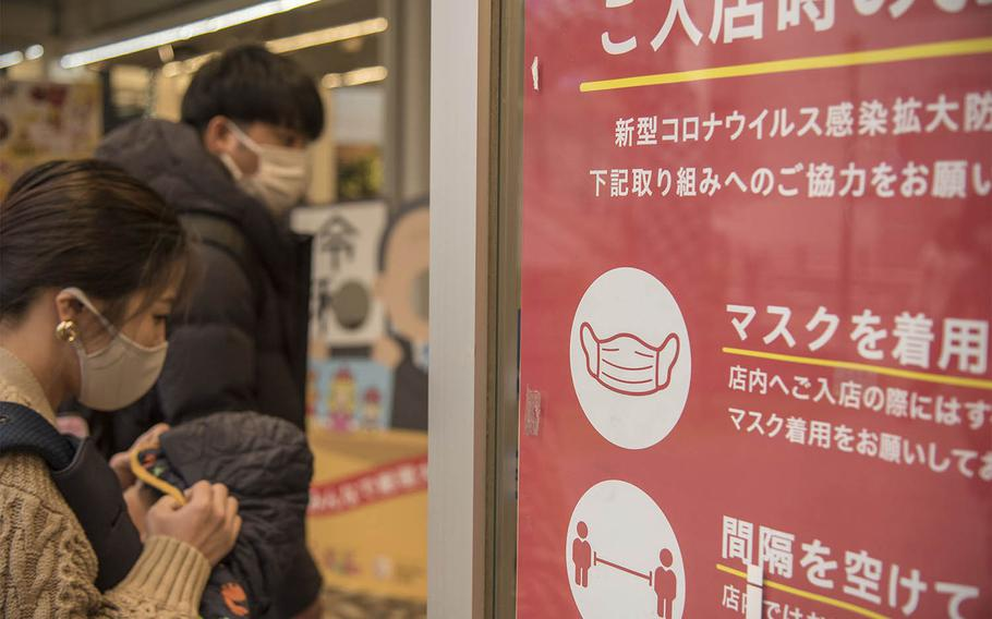 A sign reminds patrons to wear masks and practice social distancing at a shop near Kamiooka Station in Yokohama, Japan, Wednesday, Dec. 2, 2020.