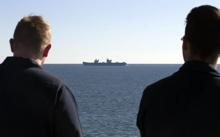 USS Gerald R. Ford sailors watch as the British Royal Navy aircraft carrier Queen Elizabeth steams through the Atlantic Ocean, Nov. 25, 2019.
