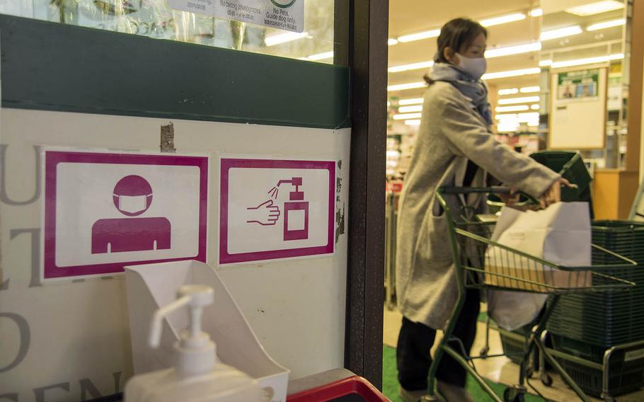 Signs warn customers to wear masks and sanitize their hands before entering a shop in Yokohama, Japan, Dec. 2, 2020.
