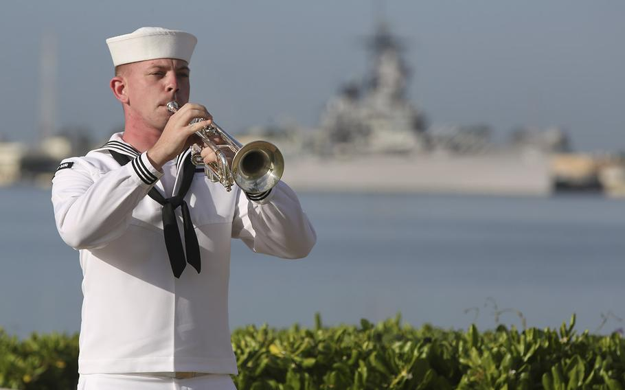 A U.S. Navy sailor plays taps in front of the USS Missouri during a ceremony to mark the anniversary of the attack on Pearl Harbor, Monday, Dec. 7, 2020, in Pearl Harbor, Hawaii.