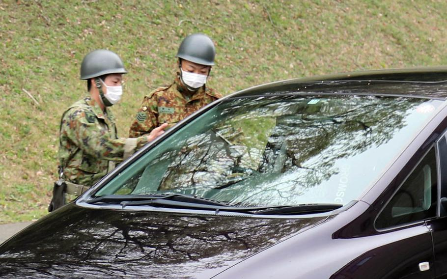 Members of the Japan Ground Self-Defense Force check a driver for coronavirus symptoms at Camp Zama, Japan, March 31, 2020.