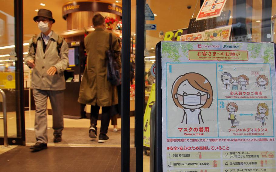 A sign reminds patrons to wear masks and practice social distancing at a shop in central Tokyo, Nov. 17, 2020.