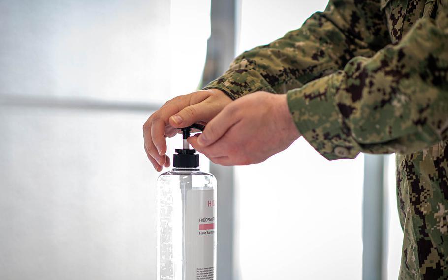 A sailor sanitizes his hands before entering the Navy Exchange at Yokosuka Naval Base, Japan, Aug. 13, 2020.