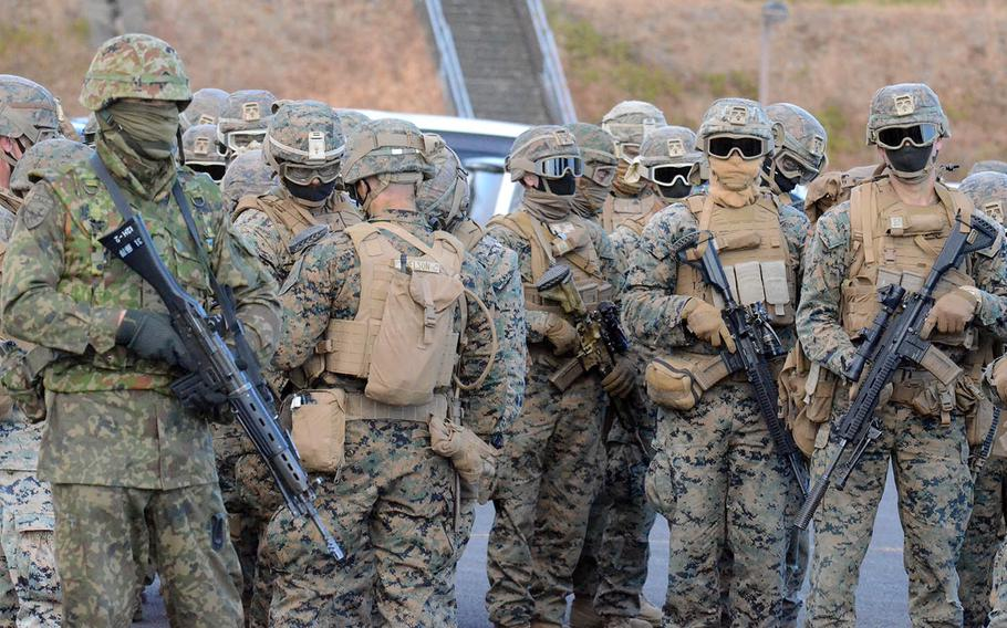 U.S. Marines and Japanese Ground Self-Defense Force soldiers prepare for an air assault exercise at Soumagahara Training Area in Gunma prefecture, Japan, Tuesday, Dec. 15, 2020.