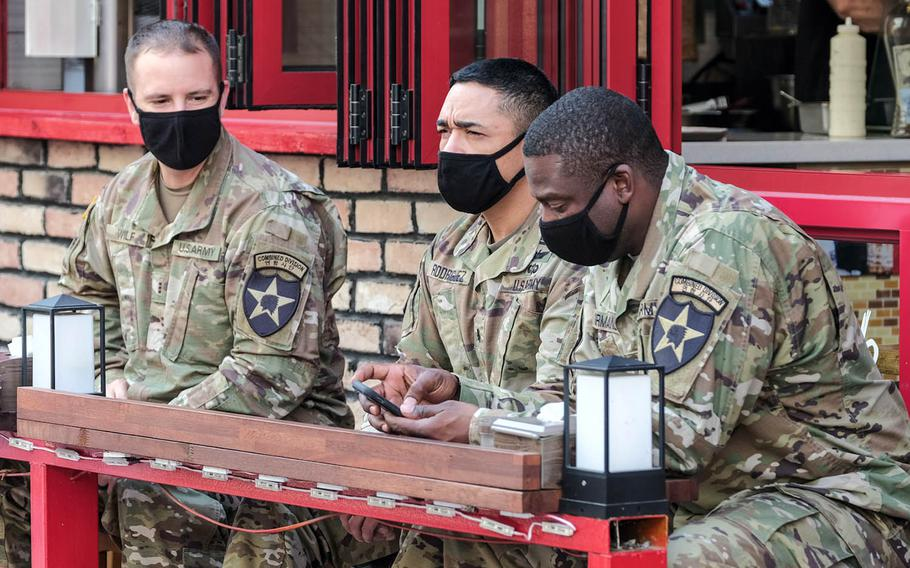 Soldiers assigned to the 2nd Infantry Division wear masks as they wait for their meals outside a restaurant near Osan Air Base, South Korea, Oct. 20, 2020.