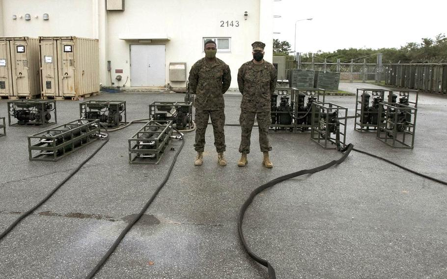 Chief Warrant Officer 3 Todd Coyle, right, and Gunnery Sgt. Alex Wright work on their Lightweight Water Purification System 3.0 at Camp Hansen, Okinawa, Dec. 7, 2020.