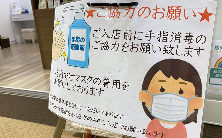 A sign outside a shop in western Tokyo reminds patrons to wear a mask and sanitize their hands, Thursday, Dec. 17, 2020.